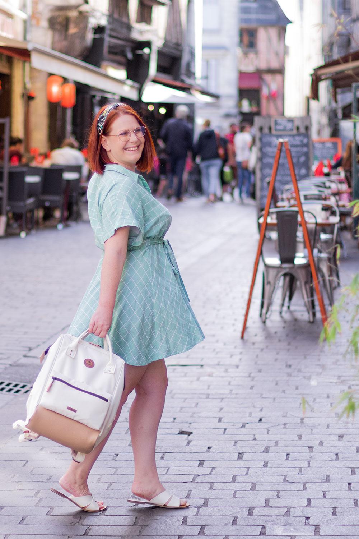 Robe verte fluide et sac à dos dans la main, en train de marcher dans la rue agitée avec le sourire