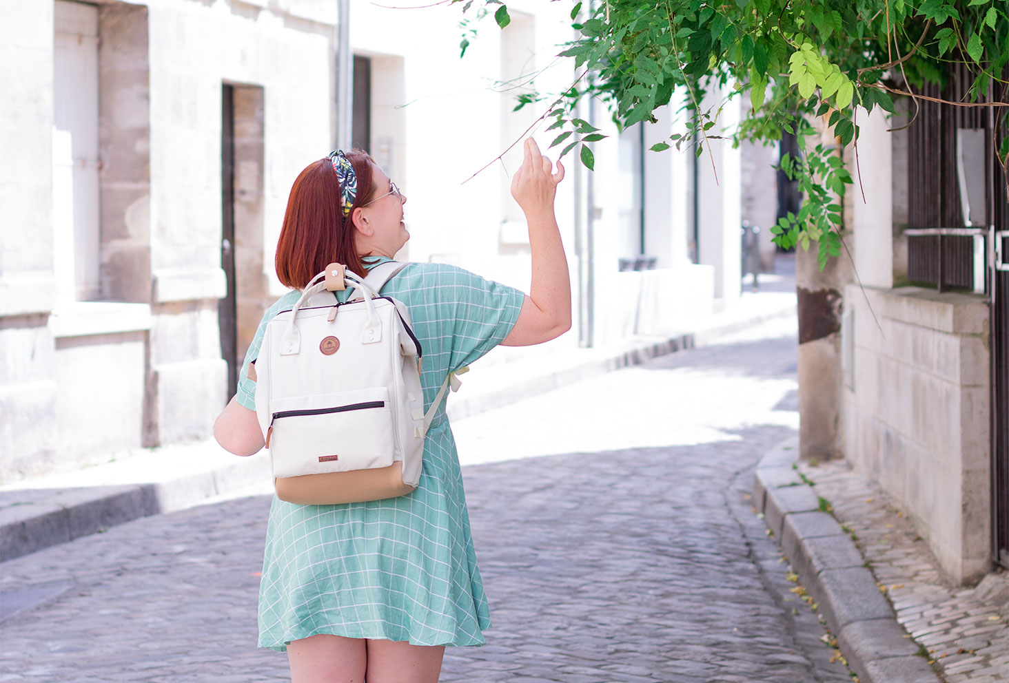 Le sac à dos beige Cabaïa porté de dos, une main dans les fleurs avec le sourire