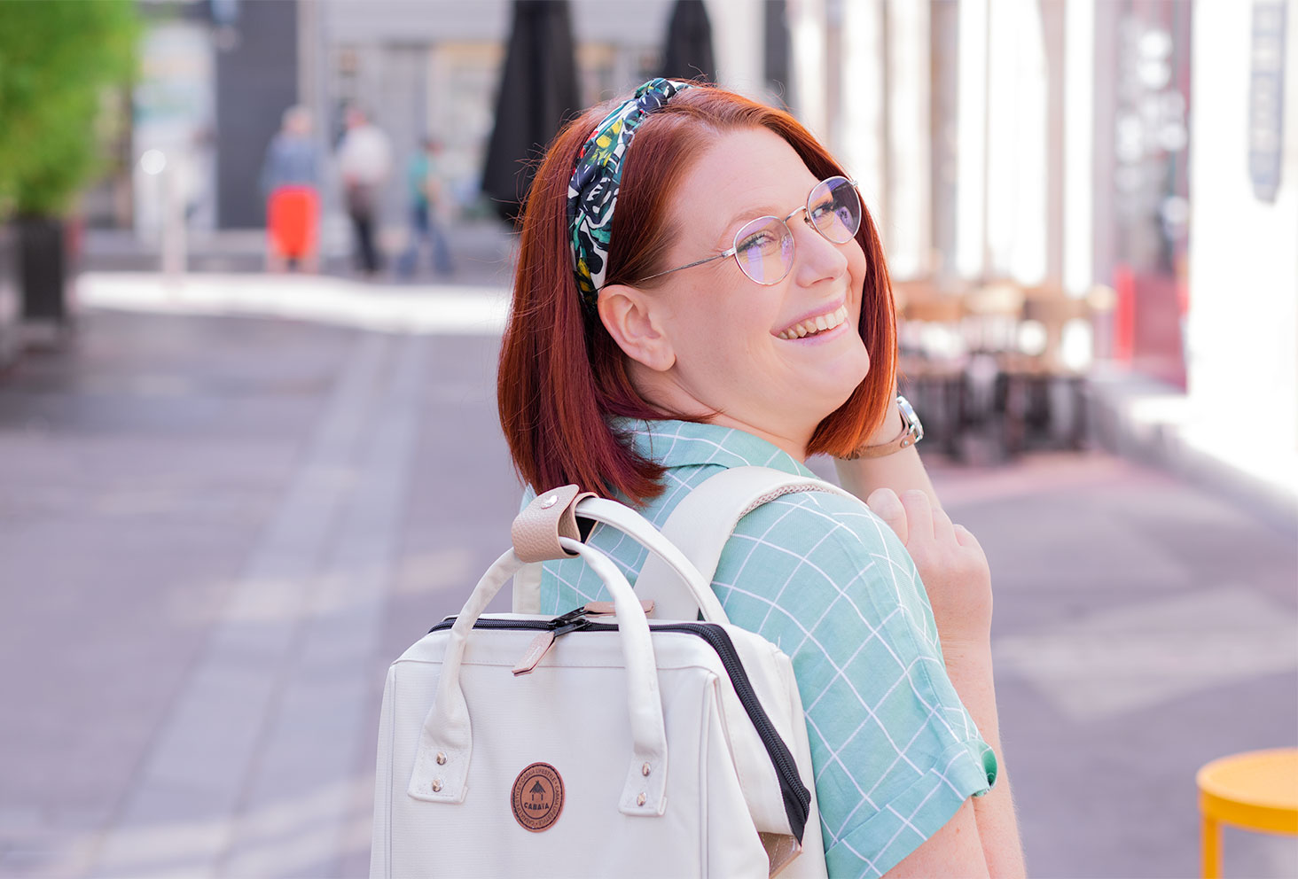 Zoom sur le haut du sac à dos beige de Cabaïa porté, avec le sourire et un bandeau fleuri dans les cheveux