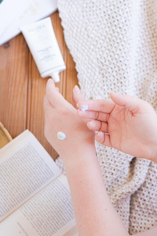 Zoom sur la texture crème blanche du masque hydratant intense de Patyla sur la main et sur le bout du doigt, au dessus du tube et d'un livre ouvert