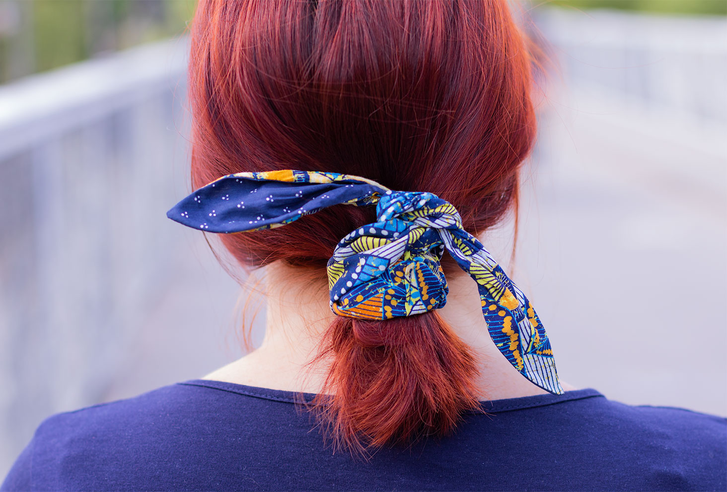 Zoom de dos sur un headband bleu noué autour d'une queue de cheval basse