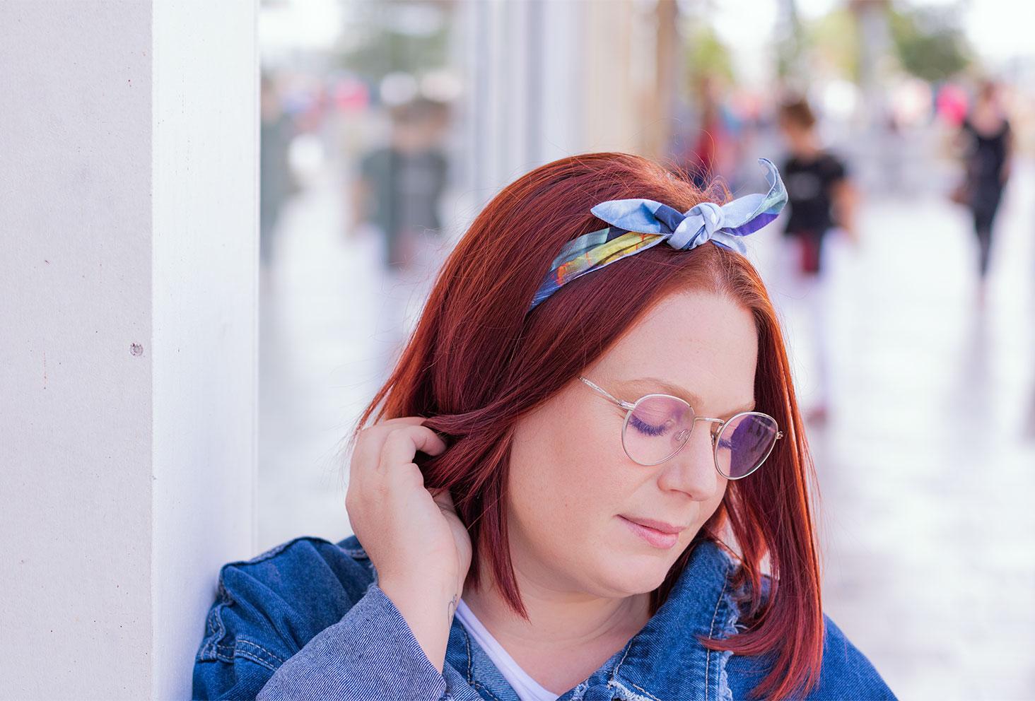 Zoom sur un bandeau bleu de La Morue noué dans les cheveux roux, la tête vers le bas une main dans les cheveux, avec un léger sourire