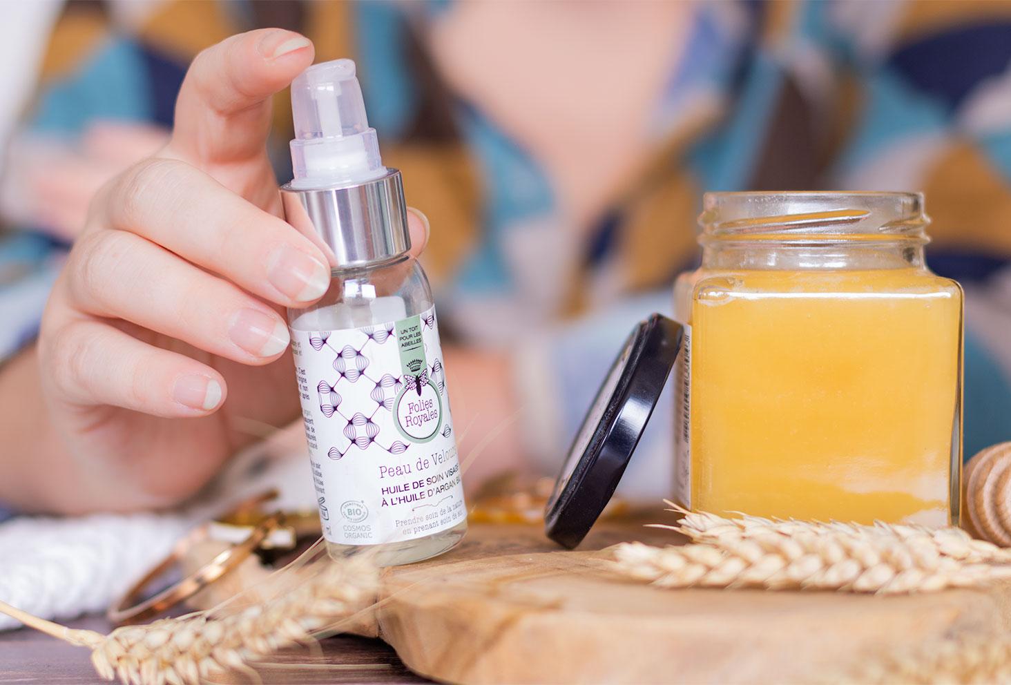 Zoom sur l'huile de soin visage de Folies Royales tenue dans la main à côté d'un pot de miel