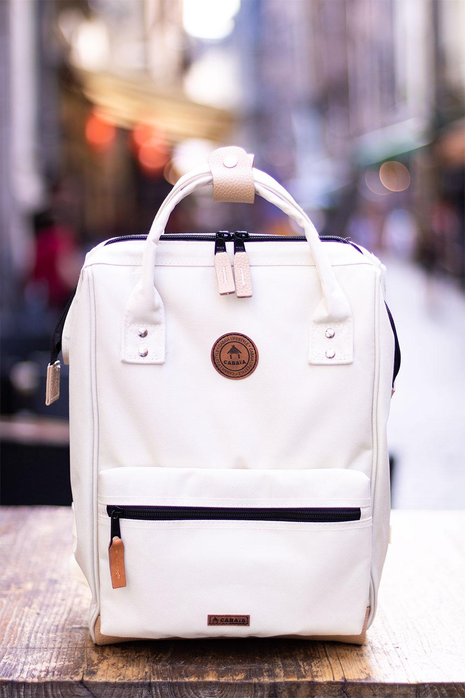 Zoom sur l'avant du sac à dos beige de Cabaïa, en tissus et en cuir, posé sur une table en bois