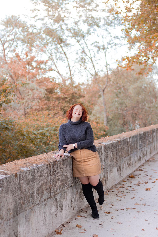 Appuyée le long d'un mur sur les bords de Loire au couleurs automnales, en jupe en jean beige et pull à col roulé, avec le sourire