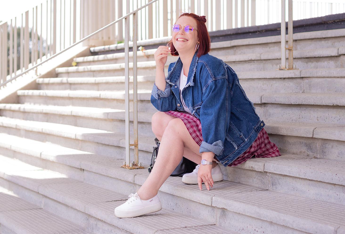 Assise dans des escaliers en béton, une main sur le sol, en veste en jean oversize et jupe à carreaux, avec le sourire et l'autre main qui tient la créole argentée
