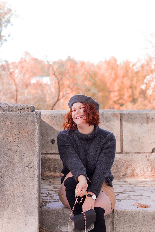 Assise sur les escaliers en pierre des bords de Loire, avec le sourire et un béret gris en laine sur la tête, en pull à col roulé et jupe en jean beige pour l'automne