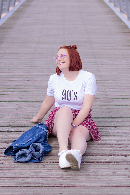 Assise sur un pont en bois le jambes étendues, en jupe écolière à carreaux et t-shirt 90's, la veste en jean posée sur le sol à côté