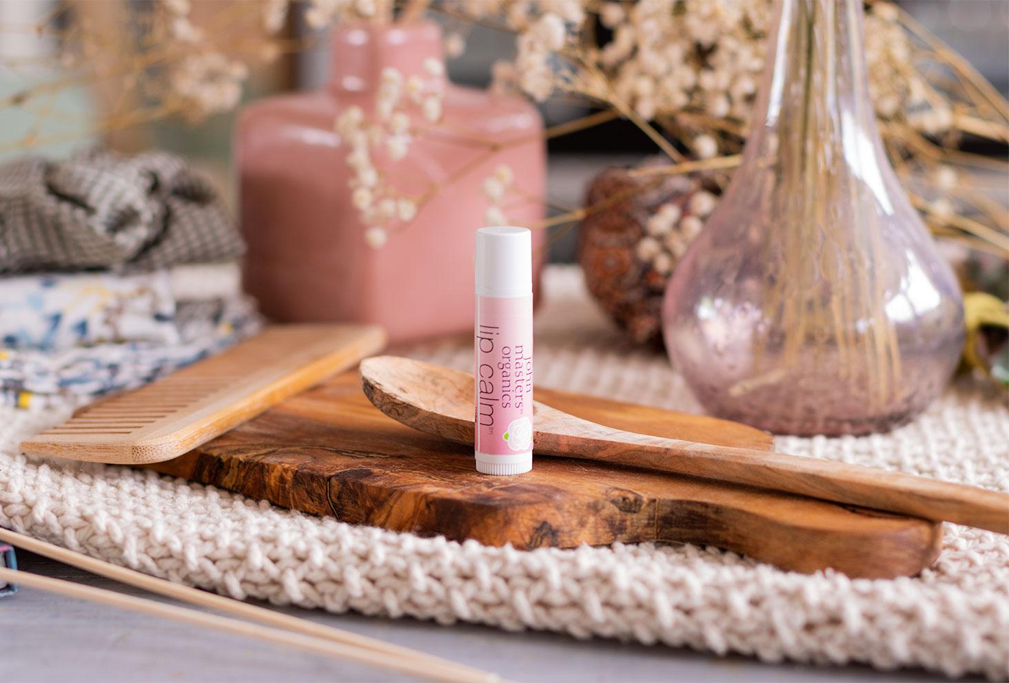 Le baume à lèvres à la rose de John Masters Organics sur une planche en bois dans un décor de salle de bain vintage, avant utilisation