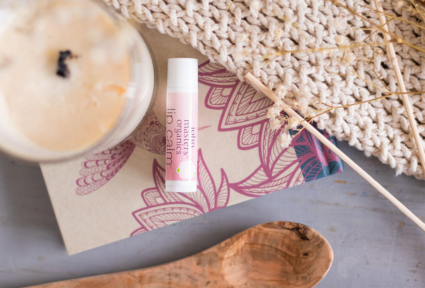 Le baume à lèvres à la rose de John Masters Organics de haut, allongé sur un livre en carton beige et rose, à côté d'une bougie et d'un plaid en mailles beiges
