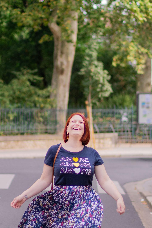 Dans une rue les bras en l'air en train de faire tourner la longue jupe fleurie Promod avec un fort sourire