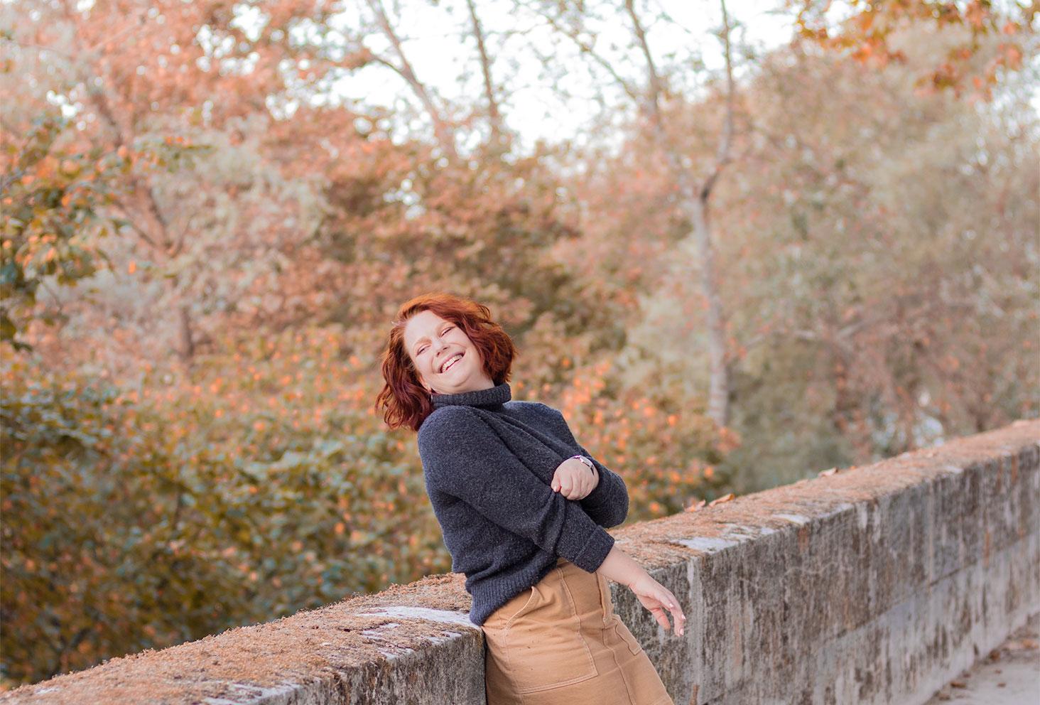 Un look d'automne avec le sourire sur les bords de Loire, en pull col roulé gris et jupe en jean beige, appuyée le long d'un mur