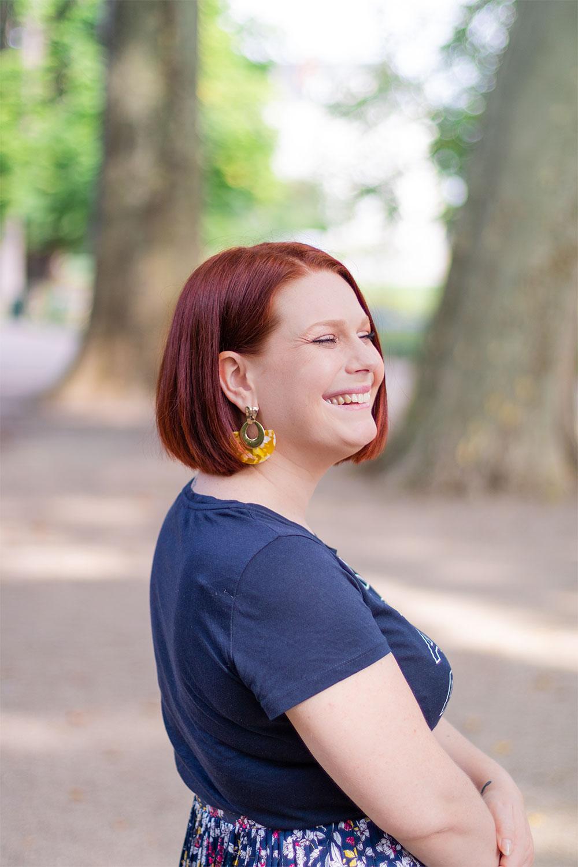 Les boucles d'oreilles jaunes portée avec un t-shirt bleu marine, de profil avec le sourire et les cheveux derrière l'oreille