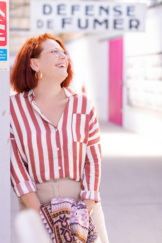 Le long d'un poteau dans un bâtiment industriel, avec le sourire en chemise rayée oversize bizzbee, un gros pull tenu entre les mains devant une jupe en velours