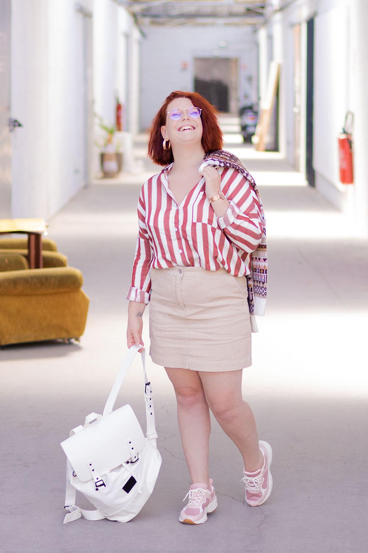 Dans un couloir industriel, en chemise à rayures et jupe en velours, avec le sourire un sac dans une main et un pull dans l'autre par dessus l'épaule