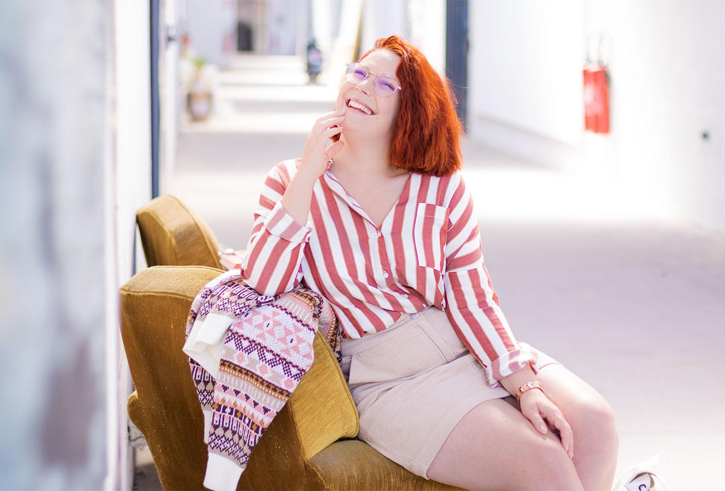 Assise sur un fauteuil vintage jaune, avec le sourire au milieu d'un couloir industriel, en chemise à rayures roses et blanches