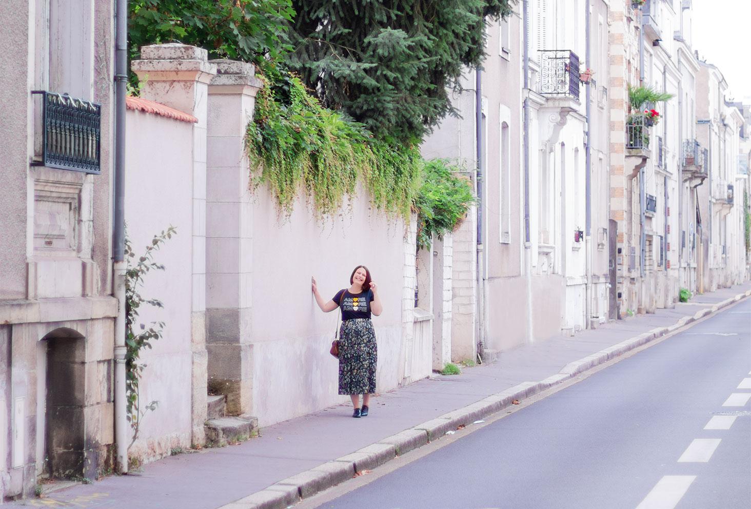 De loin sur le trottoir dans une rue tourangelle, pour un look de rentrée en longue jupe à fleurs et t-shirt plein d'amour