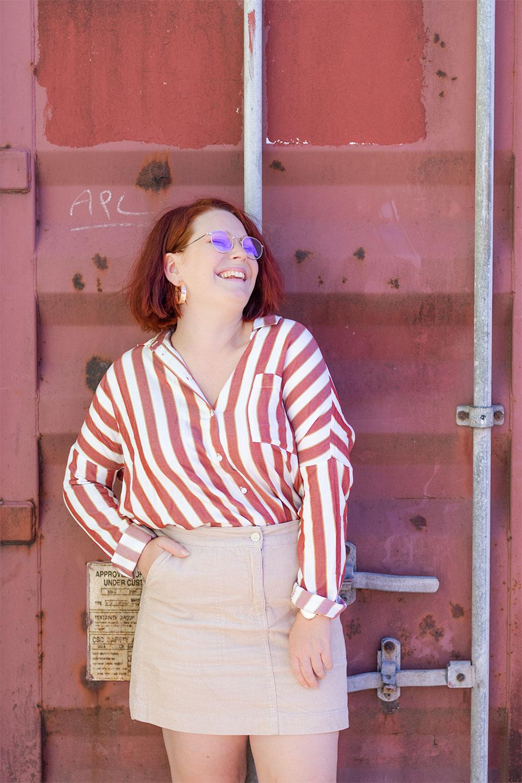 Devant une benne rosée, en chemise oversize à rayures de la même couleur