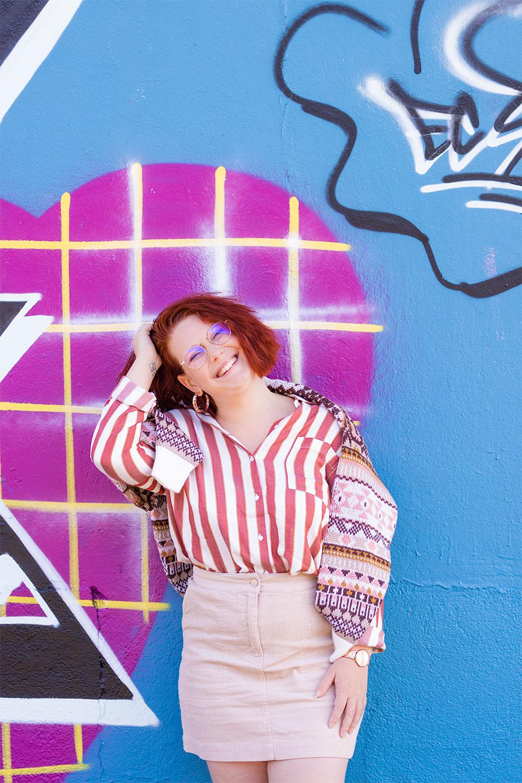 Devant un mur de graff rose et bleu, avec le sourire une main dans les cheveux, dans une chemise à rayures et une jupe en velours, un pull sur les épaules