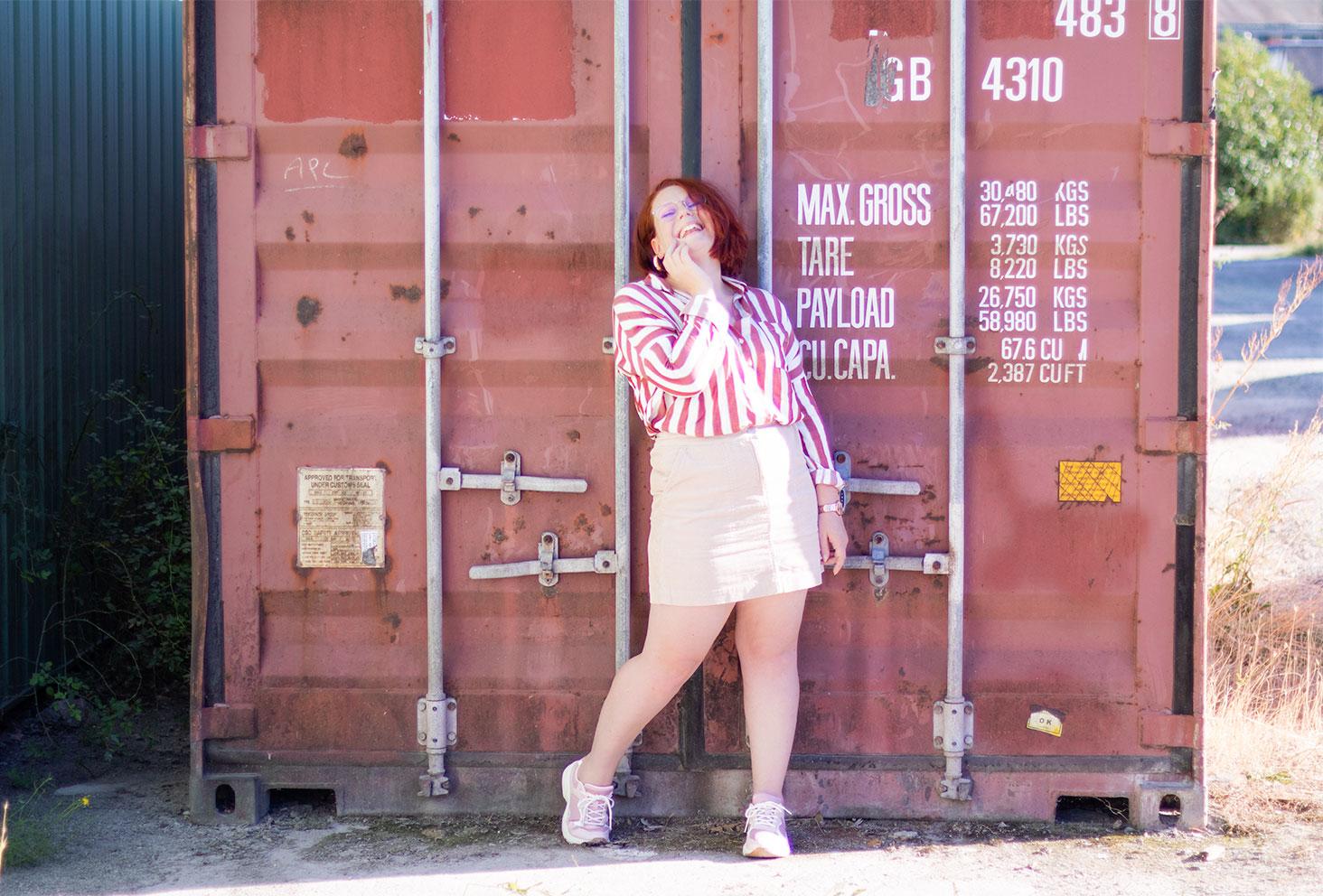 Devant une benne en look de rentrée Bizzbee, chemise oversize rentrée dans une jupe en velours beige, des baskets roses aux pieds