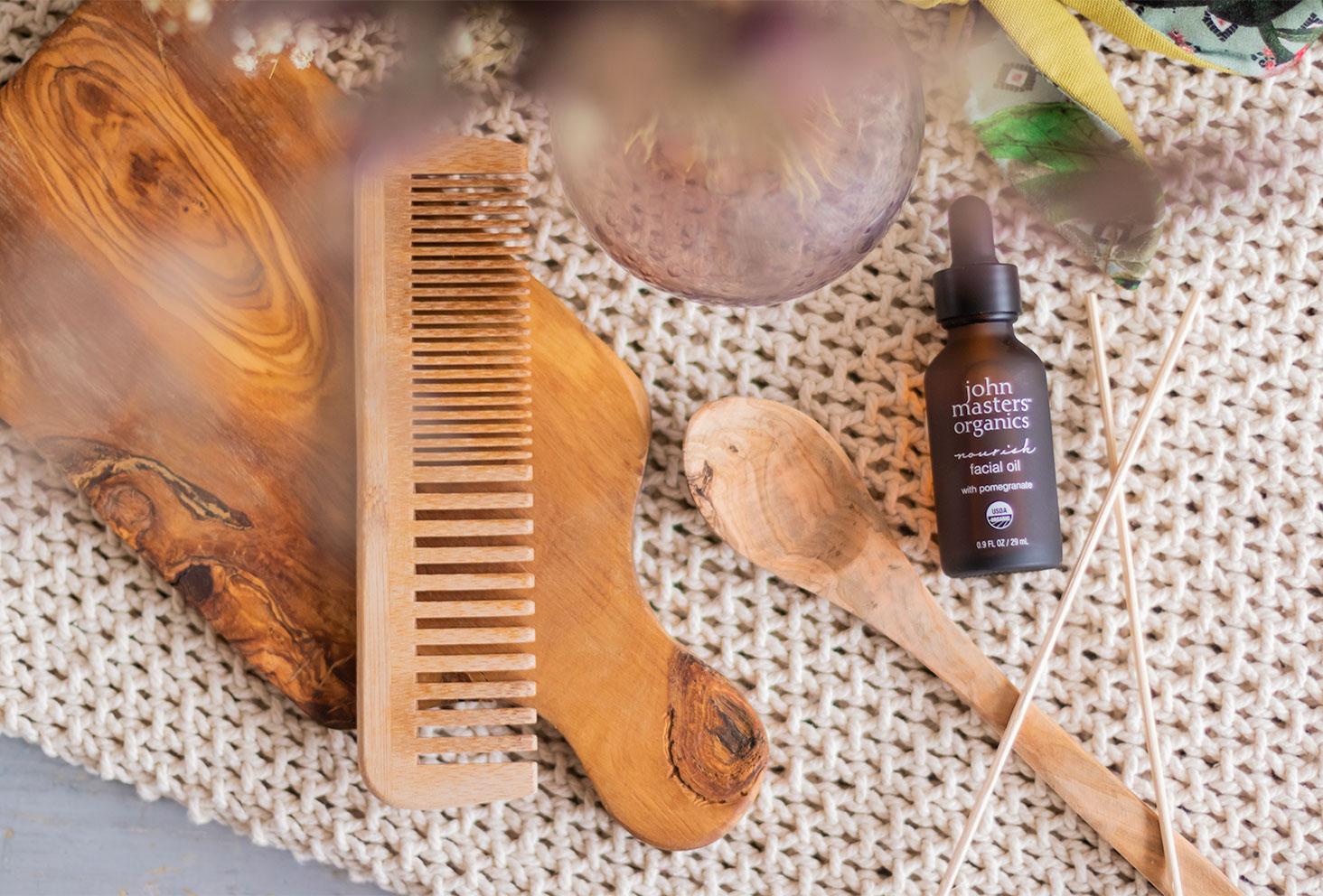 L'huile nourrissante visage de John Masters Organics de haut, allongée sur un plaid en grosses mailles beiges, à côté d'éléments de décor en bois