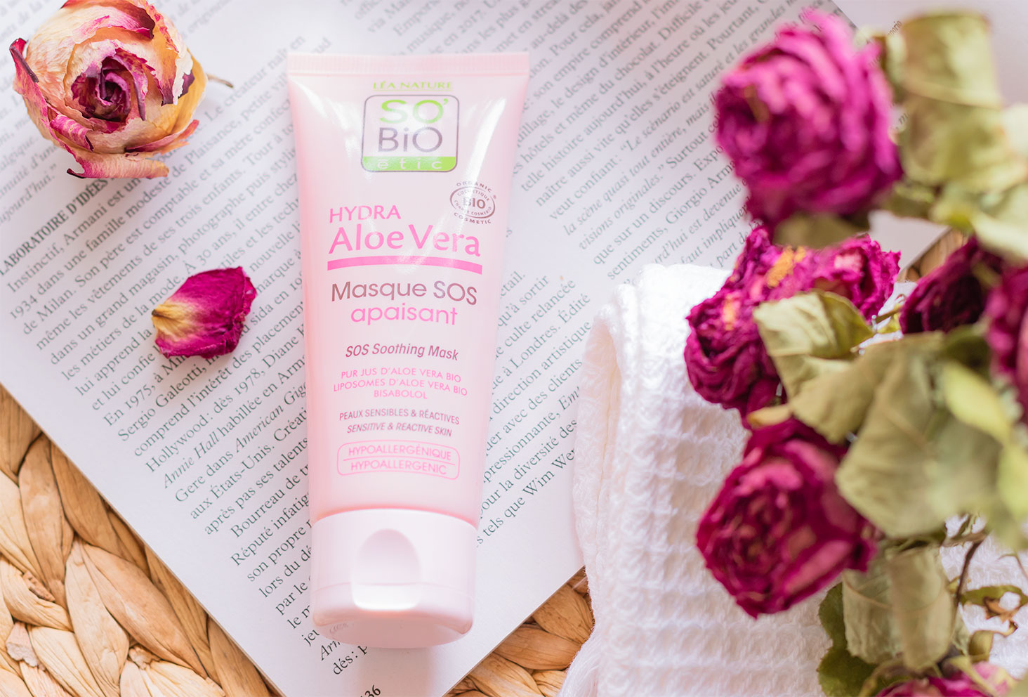 Le masque SOS apaisant dans son tube rose, posé à plat sur un magazine ouvert au milieu de fleurs séchées roses