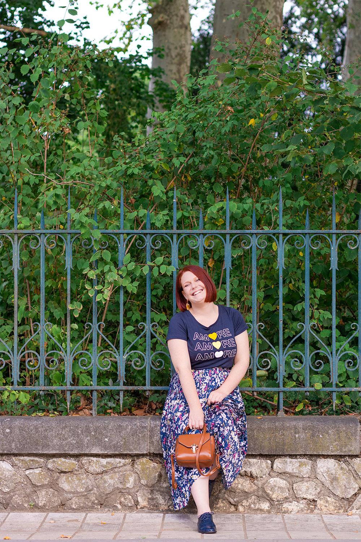 Le long des grilles du jardin des Prébendes de Tours en jupe fleurie et t-shirt bleu aux motifs Amore avec le sourire