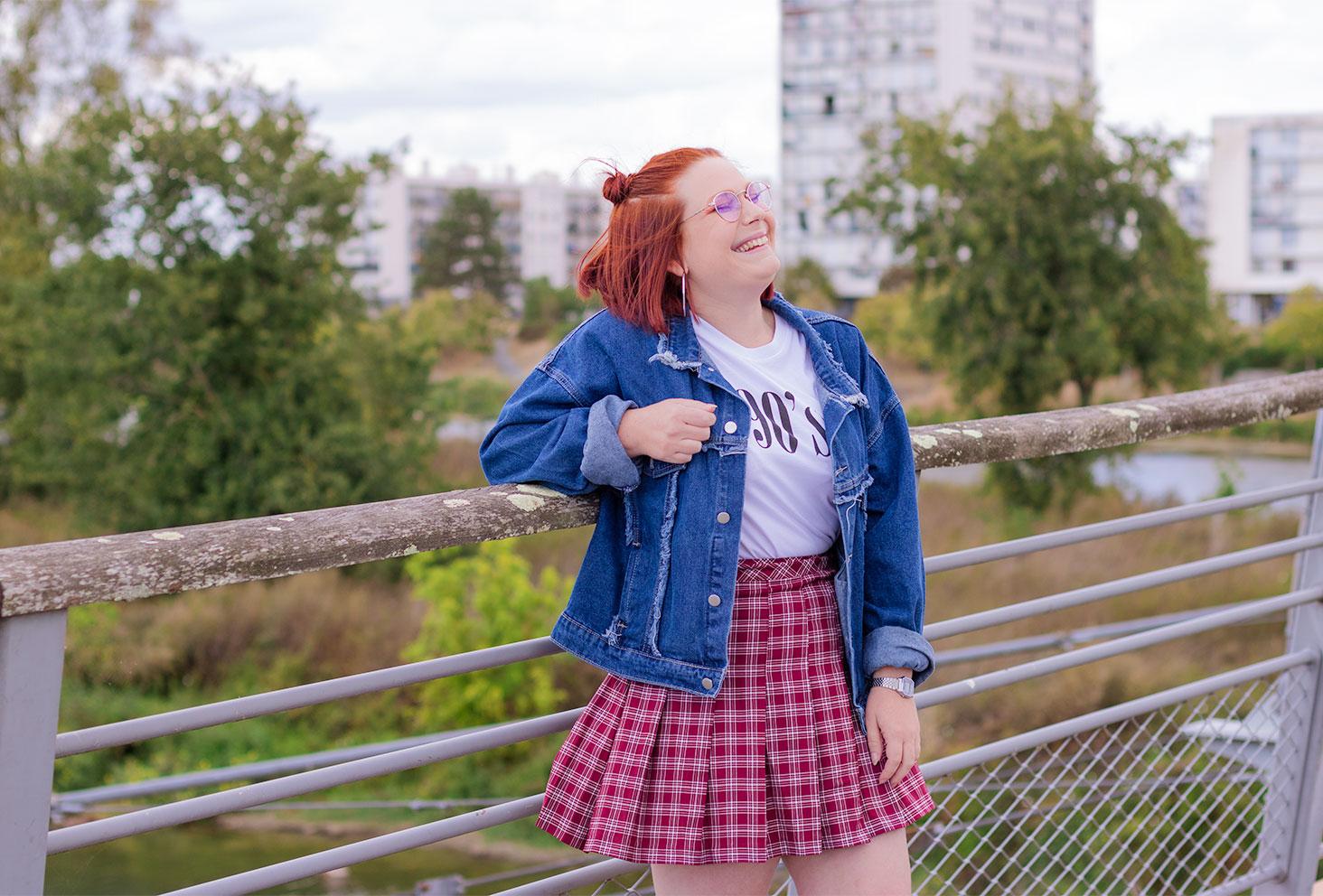 Appuyée le long d'une rambarde en bois et métal, avec le sourire, en veste en jean bleue à franges et jupe bordeaux à carreaux