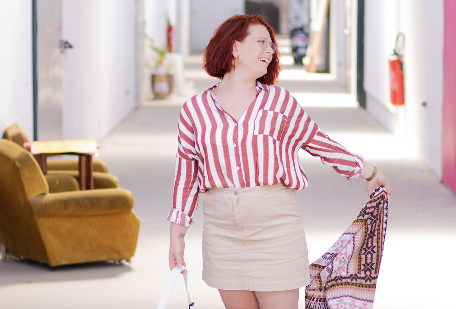 En chemise à rayures entrée dans une jupe en velours beige, au milieu d'un couloir industriel, pour un look parfait pour la rentrée