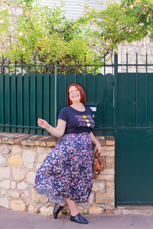 En longue jupe qui tourne fleurie pour la rentrée, avec le sourire le long d'un mur de pierre et de grilles vertes