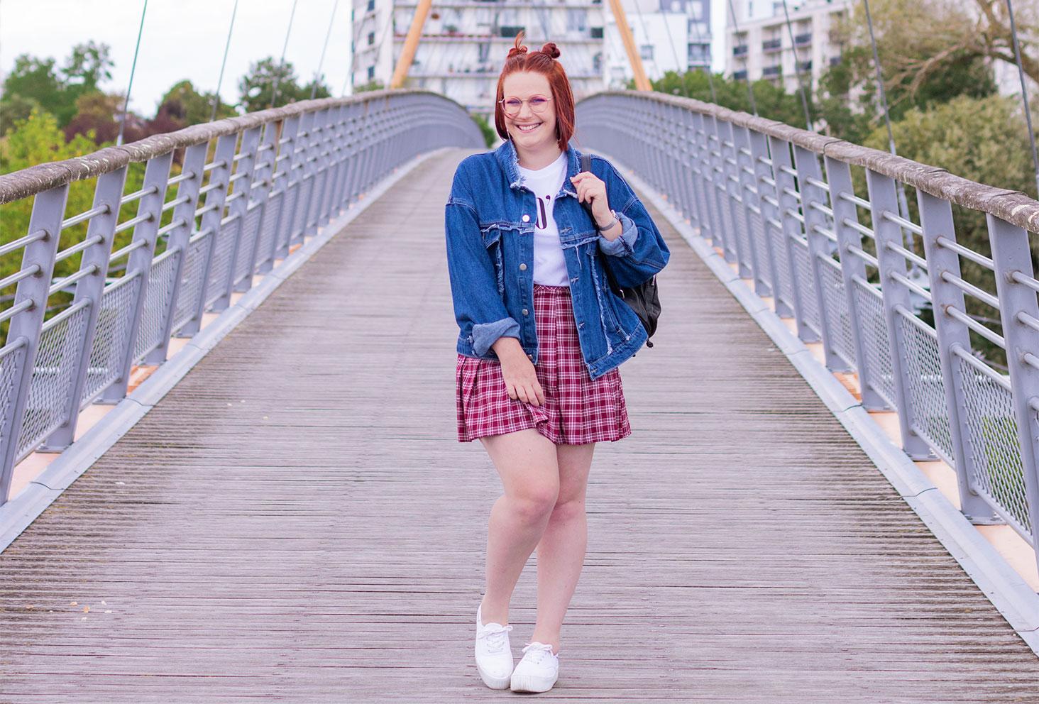 Au milieu d'un pont suspendu en look 90's vintage, jupe écolière et veste en jean oversize avec un sac à dos noir sur l'épaule