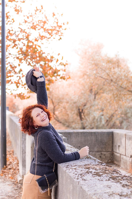 Appuyée le long d'un mur en pierre, une main en l'air avec le béret au bout, avec le sourire sur les bords de loire aux couleurs de l'automne
