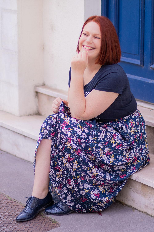 Assise sur des marches en marbre devant une porte d'entrée bleue, avec le sourire et une main sur le menton, en jupe longue bleue à fleurs, t-shirt bleu marine et derbies de la même couleur