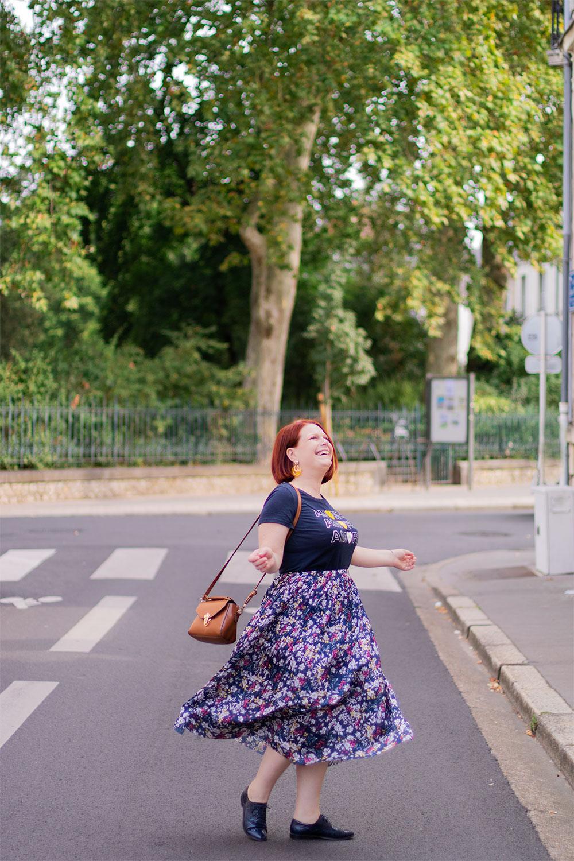 Au milieu d'une rue devant l'entrée d'un parc, en train de faire tourner sa longue jupe fleurie et son petit sac marron, avec le sourire