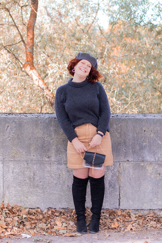 Look automnal devant un muret en jupe en jean beige et pull à col roulé gris, des cuissardes aux pieds et un béret sur la tête, avec le sourire