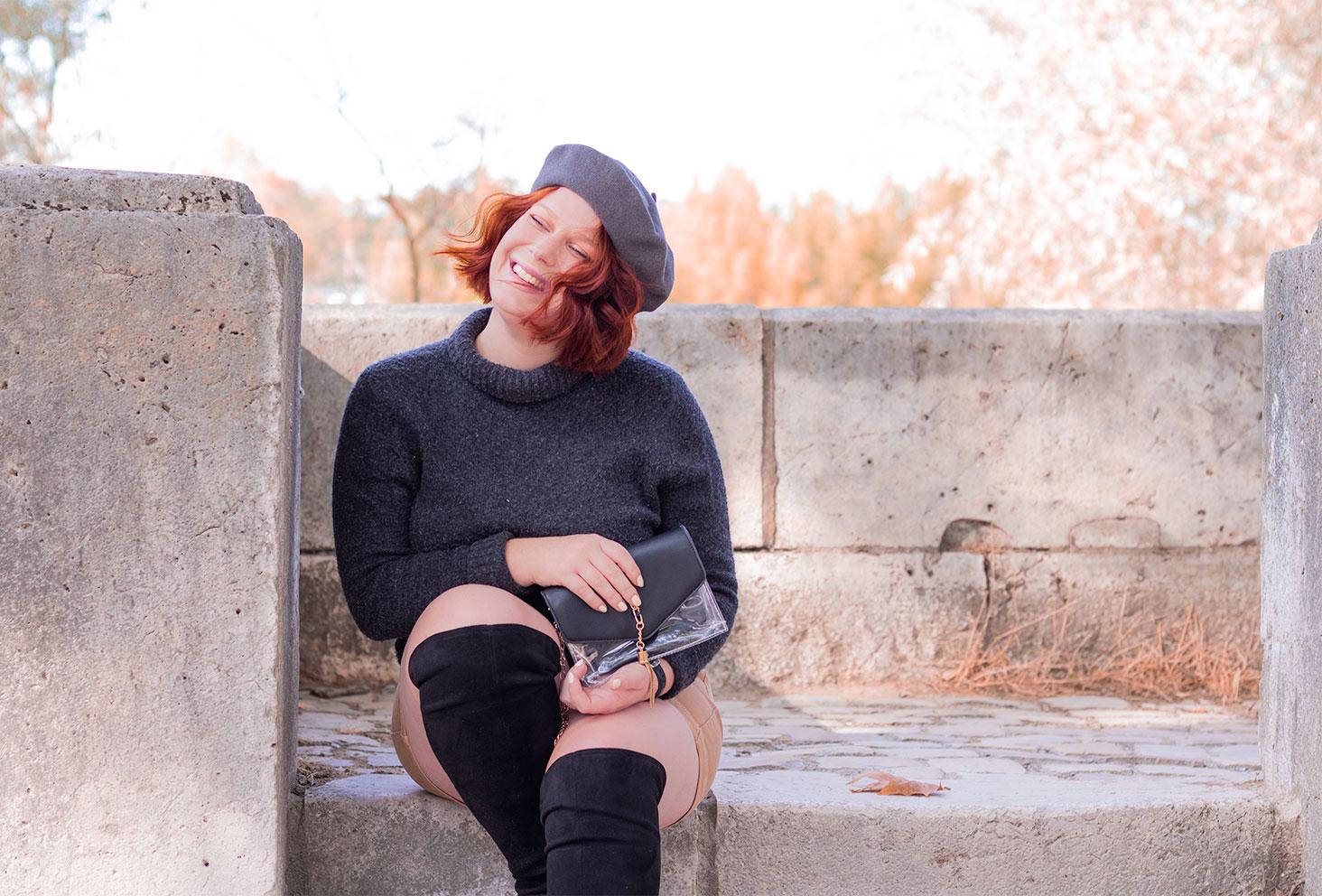 Assise dans un escaliers en pierre avec le sourire, un béret sur la tête en pull à col roulé