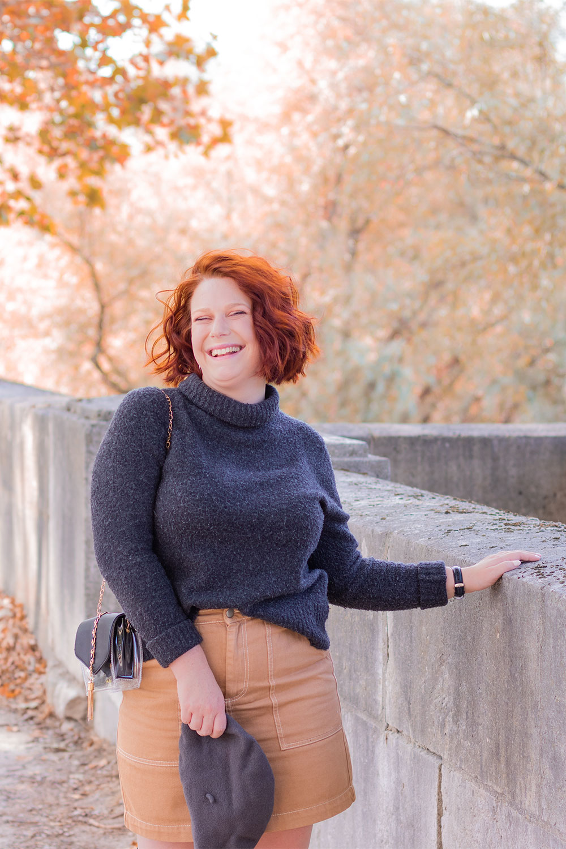 Avec le sourire, la main appuyée le long d'un mur en pierre, en pull gris et jupe beige
