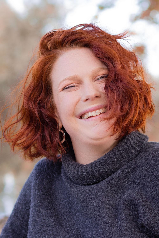 Photo portrait automnal, cheveux bouclés roux avec le sourire, en pull gris à col roulé