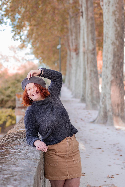 Look d'automne dans une allée des bords de Loire à Tours, appuyée avec le sourire le long d'un mur en pierre, une main sur le béret en pull gris et jupe beige