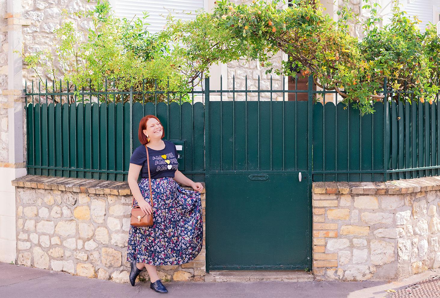 Dans le coin d'une rue devant un joli portail vert et fleuri, en longue jupe fleurie bleue, avec le sourire accoudée le long d'un mur de pierres