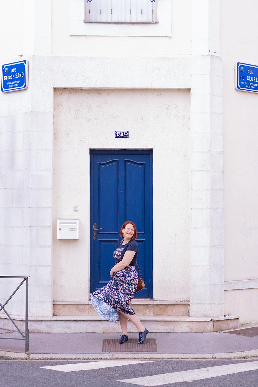 Devant une porte bleue en train de faire voler sa longue jupe fleurie pour un look de la rentrée 2019