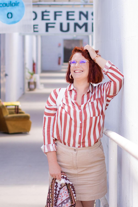 Dans un local industriel, en chemise à rayures et jupe en velours beige Bizzbee, une main dans les cheveux le long d'une rampe blanche