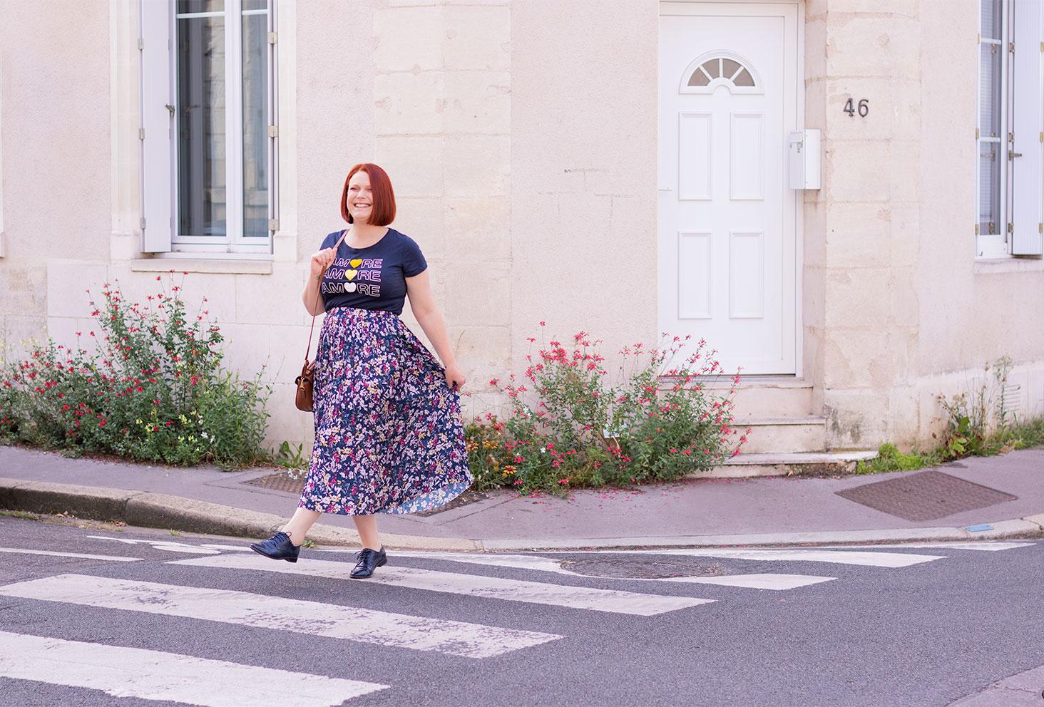 Sur un passage piéton en train de traverser la rue dans une longue jupe fleurie bleue et un t-shirt aux inscriptions Amore
