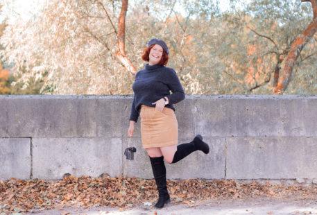 Sur les bords de Loire en pull à col roulé, jupe beige, cuissardes et béret sur la tête, avec le sourire et une jambe en l'air