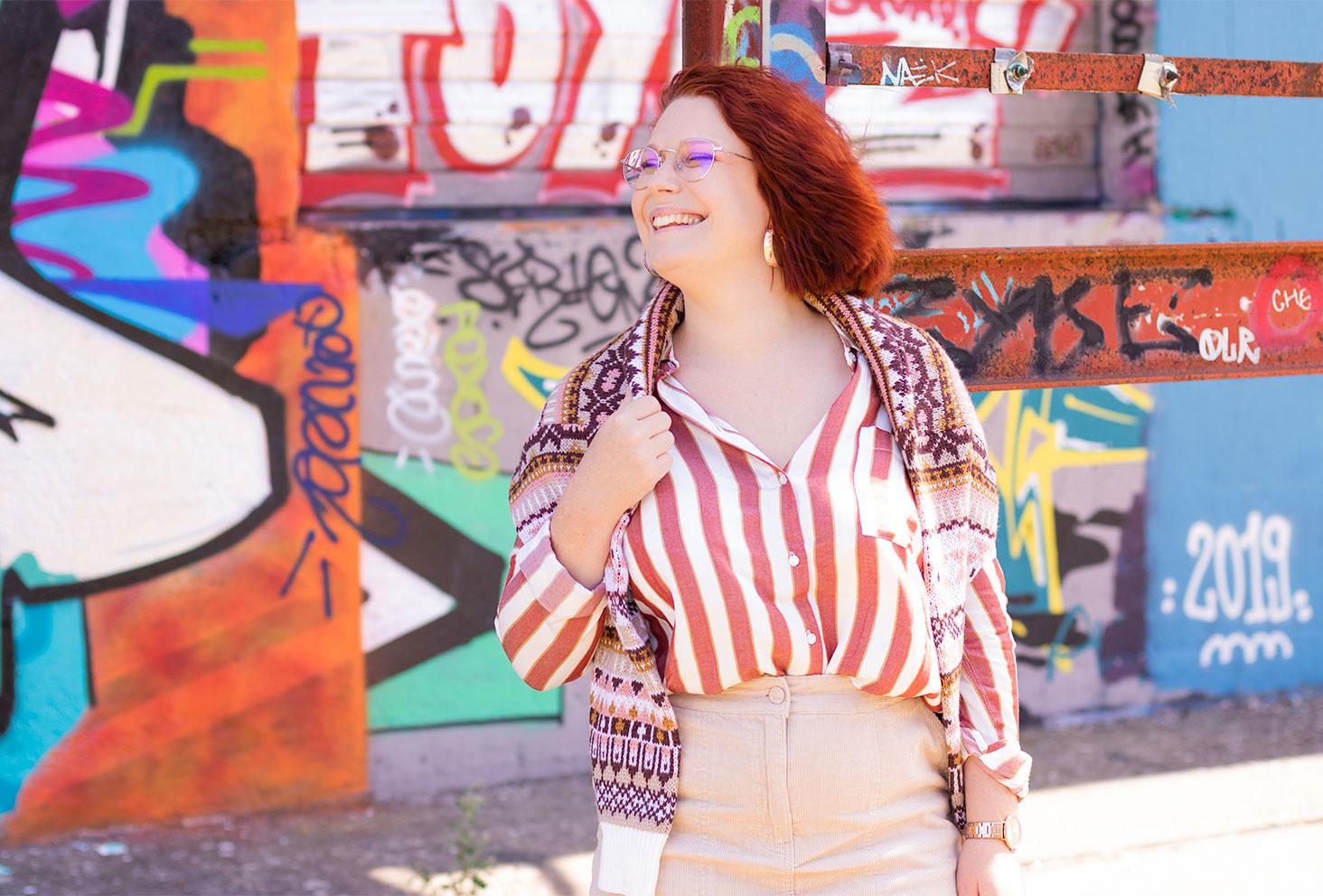 Devant un mur de graffitis coloré en total look bizzbee, de profil avec le sourire