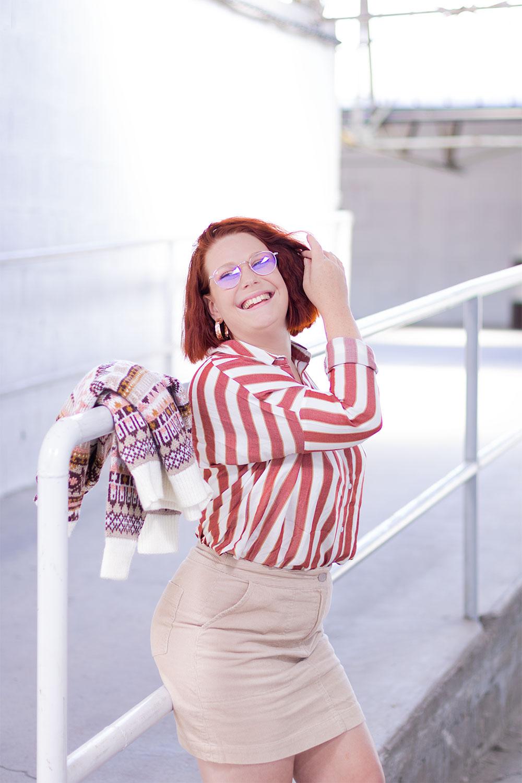Total look de rentrée Bizzbee, appuyée le long d'une rambarde avec une main dans les cheveux et avec le sourire