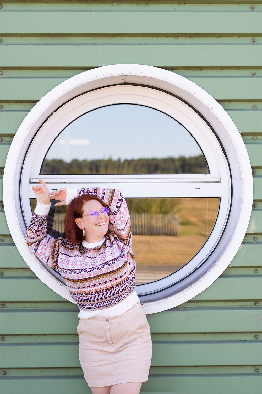 Appuyée le long d'une fenêtre en forme de hublot, sur un mur vert en métal, dans un gros pull d'hiver et une jupe en velours beige