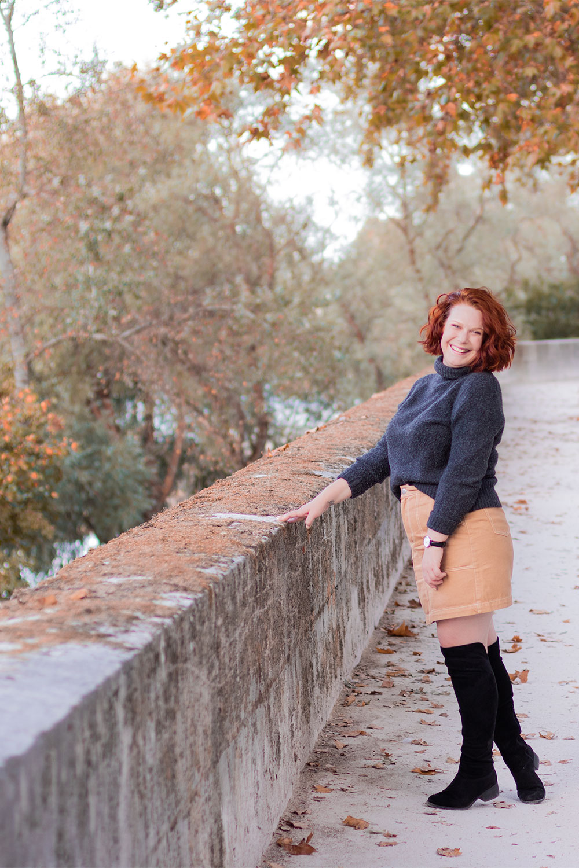 Appuyée le long d'un mur en pierre dans un décor automnal des bords de Loire, avec le sourire pour un look de rentrée en automne