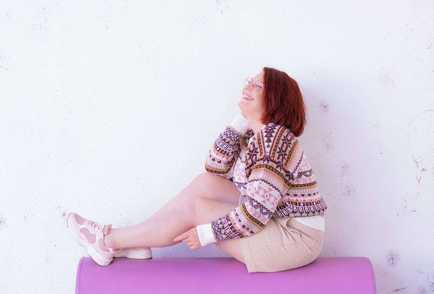 Assise sur un canapé rose, en couleurs beiges et pastels, avec le sourire de profil le long d'un mur blanc