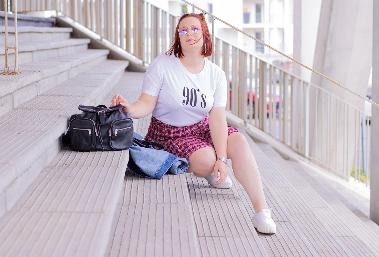 Look 90's vintage et street, assise dans des marches en béton gris